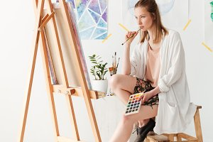 Concentrated young caucasian lady painter at workspace