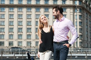 Pretty couple of cheerful man and woman walking in street
