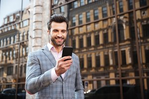 Happy handsome man in jacket looking at mobile phone