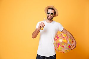 Cheerful young man holding beer and beach ball.