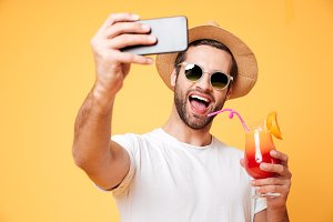 Smiling young man make selfie by phone holding cocktail.
