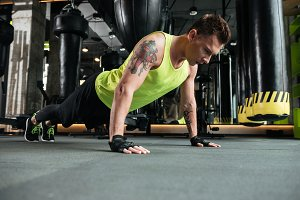 Concentrated young sportsman make sport exercises in gym