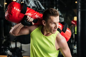 Sportsman holding punching bag on his shoulder in gym