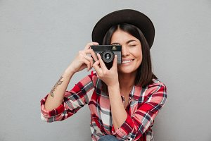 Funny young asian woman isolated over grey wall holding camera.