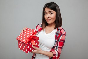 Young sad woman holding gift over grey wall.