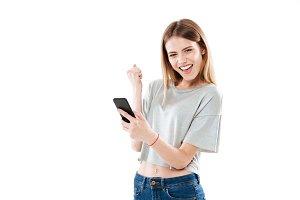 Happy joyful girl holding mobile phone and celebrating a win