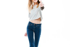 Pretty cheerful girl standing and showing thumbs up gesture
