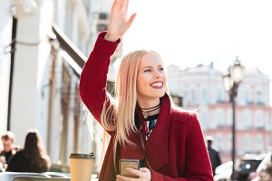 Happy young caucasian woman sitting in cafe chatting and waving