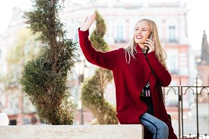 Happy young caucasian woman talking by phone waving to friends.