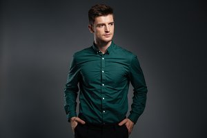 Attractive serious man dressed in shirt posing