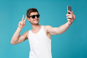 Happy man make selfie by phone showing peace gesture.