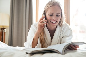 Young blonde woman reading magazine and talking on phone