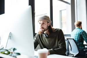 Young handsome man work in office using computer