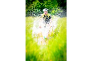 Mountain Biker Riding Through A Large Puddle