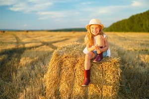 Little girl in a field with hay rolls