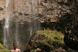 Young man at waterfall