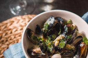 Mussels in sashes in sauce in a bowl on a napkin