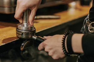 Close-up of barista temping coffee