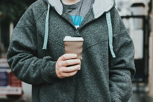 Closeup on man holding paper cup