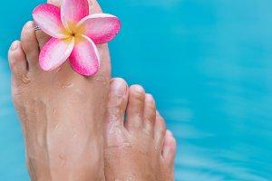female legs blue pool water frangipani flower