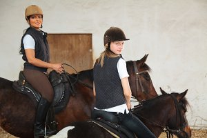 Girl And Young Woman In Indoor Riding Arena