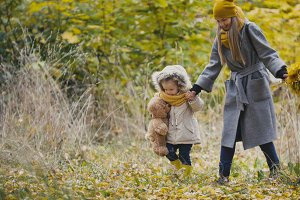 Baby girl with her mommy walking in autumn park