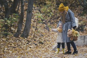 Woman with little daughter in autumn park among yellow leaves