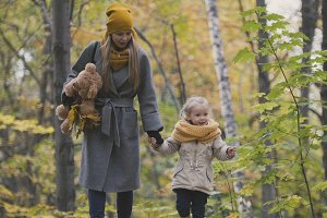 Mother and her daughter little blonde girl walking in a autumn park