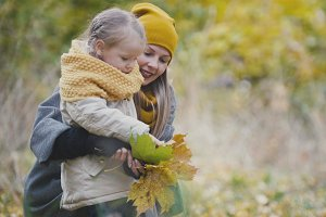 Mommy and daughter in autumn park plays with yellow leaves