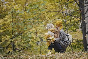 Mother and daughter together among yellow leaves in autumn park