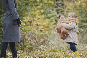 Pretty blonde little girl in autumn park plays with teddy bear
