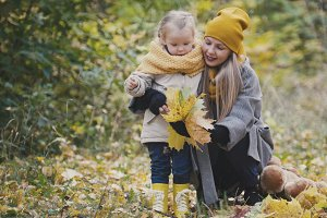 Mother and daughter in park, among yellow leaves