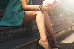 woman with beauty leg holding a book
