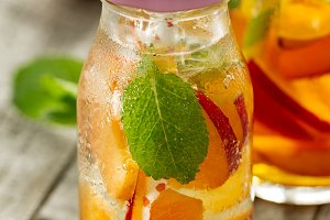 Tasty cold drink with fruit and mint