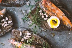Sardines, quail egg on rye bread closeup