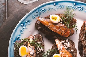 Sardines, quail egg on rye bread and the glass