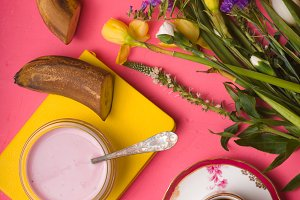 Breakfast with yoghurt, coffee and a bouquet of flowers