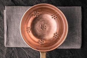 Copper colander on the stone