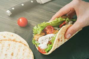 Hand holding mexican fajita wrap with chicken meat and vegetables. Toned image.