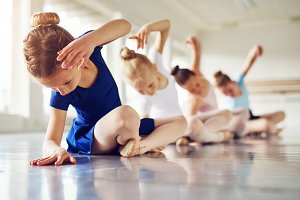 Girls bending sitting on floor in ballet class