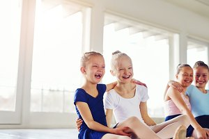 Little ballerinas having fun and embracing in ballet class