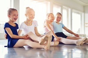 Smiling girls having fun on floor of ballet class