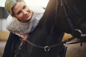 Smiling blonde female sitting astride black horse