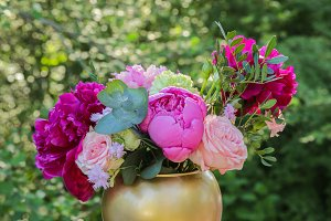 Bouquet of peonies in a golden vase