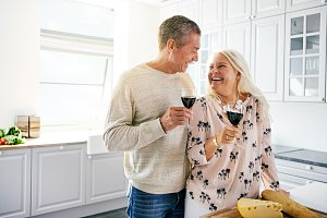 Laughing retired couple drinking a glass of wine