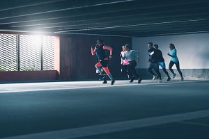 Group of determined young athletes urban running