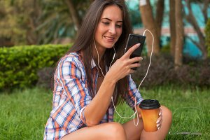 Attractive young woman in headphones listening to music using a smartphone and drinking coffee while sitting on curb outdoors in the city center