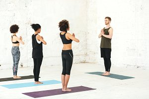 Group of multicultural women practicing yoga with male instructor