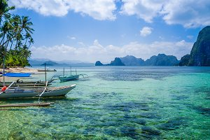Banca boats in clear water at sandy beach in El Nido, Philippines