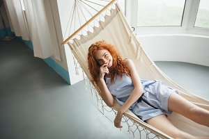 Cute cheerful young redhead lady lies on hammock